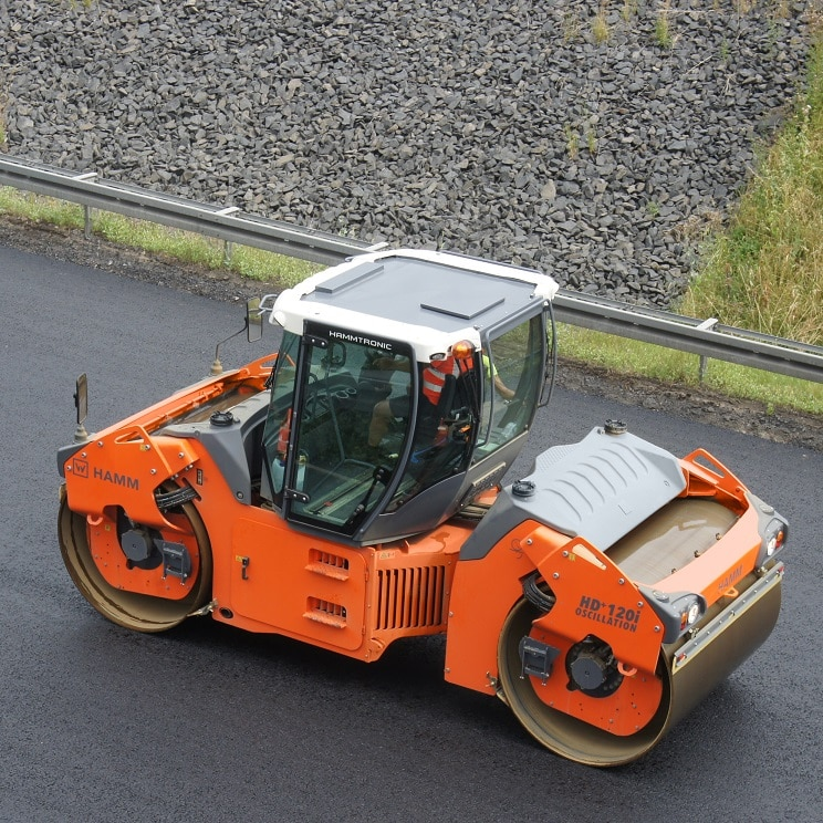 A HAMM HD+ 120i OV tandem roller compacting the surface course of a busy highway.